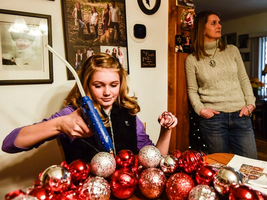 With her mother nearby, Daphne Parker glues items to a wreath she is working on at her kitchen table.