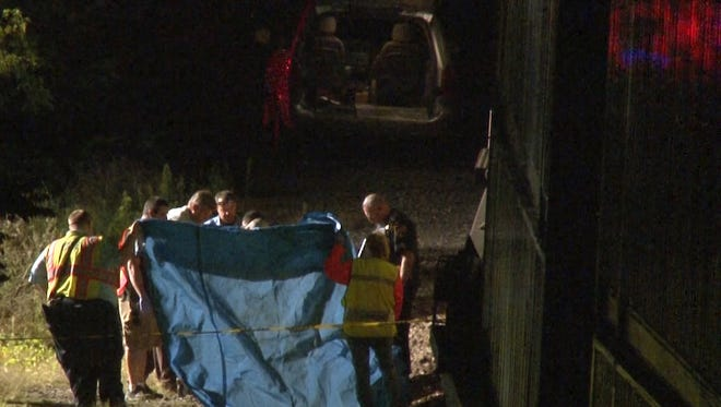 First responders and police officers lift a blue tarp covering the body of a man killed after being struck by a train in Waverly Monday night.