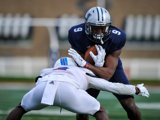 Monmouth University wide receiver Reggie White Jr. braces for impact against Presbyterian's Rock Ya-Sin during Saturday's game in West Long Branch on Nov. 4, 2017.