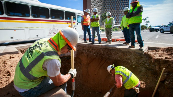 Sam Myers (left) and others with Achen-Gardner Construction dig around an old, unmarked pipe they discovered under University Drive in Tempe in 2013.