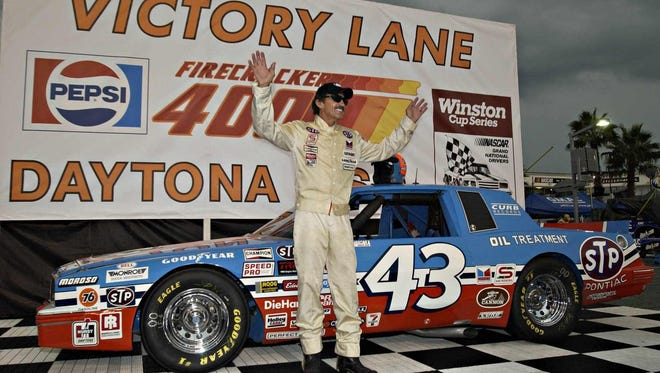 Richard Petty stands with his signature NO. 43 racecar.