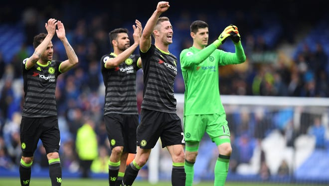 Chelsea's English defender Gary Cahill (2R) and teammates celebrate victory after the English Premier League football match between Everton and Chelsea at Goodison Park.