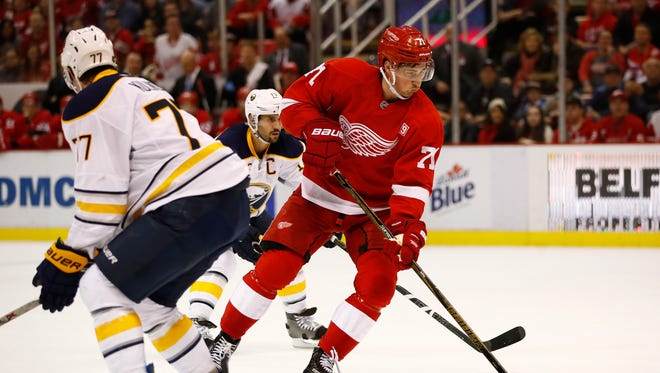 Dylan Larkin #71 of the Detroit Red Wings tries to control the puck near Dmitry Kulikov #77 of the Buffalo Sabres during the second period at Joe Louis Arena on December 27, 2016 in Detroit, Michigan.