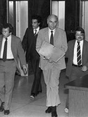 In this Jan. 22, 1983 file photo, ex-CIA agent Edwin Wilson, center, leaves federal court after a day of jury selection accompanied by U.S. Marshals in Houston.