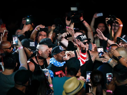 Fans cheer as Floyd Mayweather Jr., center, arrives for a news conference at Staples Center on Tuesday, July 11, 2017, in Los Angeles. Mayweather Jr. is scheduled to fight Conor McGregor in a boxing match in Las Vegas on Aug. 26. (AP Photo/Jae C. Hong)