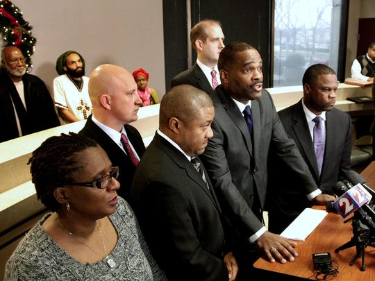 In this 2014 file photo, (in the front row from left to right) John Crawford III's mother Tressa Sherrod, attorney Michael Wright, Crawford's father John H. Crawford Jr. and attorney Shean Williams discuss the filing of a federal civil rights and negligence lawsuit during a news conference in Dayton, Ohio.