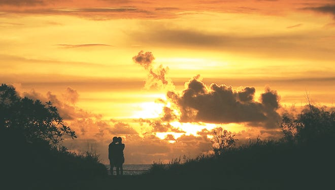 A couple takes in the deep amber colors of the sunset on Aug. 13, 2014, from War in the Pacific National Historical Park Asan Beach Unit.