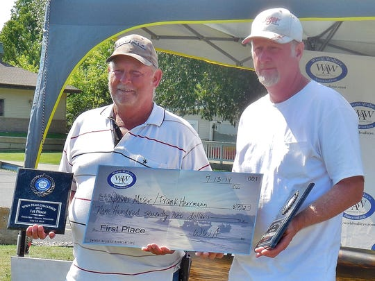 James Moser and Frank Hermanns hold their plaque and oversize check for first place after winning the World Walleye Association Tournament in Oconto on July 13.