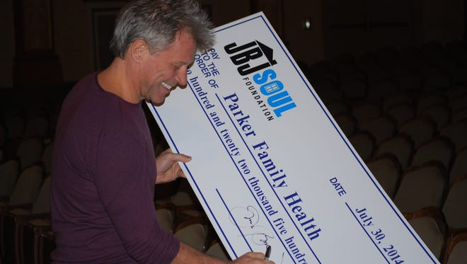 Jon Bon Jovi signs a check for the Parker Family Health Center at the Count Basie Theatre in Red Bank on Monday, Dec. 22.