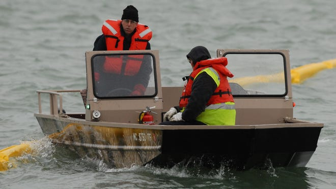 Enbridge employees place a containment boom in the St. Clair River near Marysville during a training exercise on Wednesday.