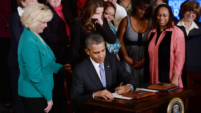 President Barack Obama signs executive orders on equal pay April 8, 2014, as women look on at the White House in Washington.