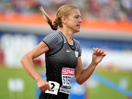 FILE - This is a Wednesday, July 6, 2016 file photo of Russian doping whistleblower Yulia Stepanova as she runs under a neutral flag  while  she competes in a women's 800m heat during the European Athletics Championships in Amsterdam, the Netherlands. The International Olympic Committee said Monday Oct. 24, 2016 that  it is offering career assistance to the Russian  wife and husband team  of Yulia Stepanova and  Vitaly Stepanov who blew the whistle on widespread doping in their homeland. (AP Photo/Geert Vanden Wijngaert. File)