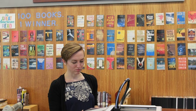 Assistant Librarian Gabby Cox gets the front desk in order at the Cedar City Library June 2, 2018.
