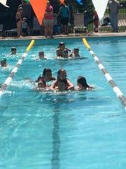 GHS alumnus and swimmer Daniel Alvarez swims with children.
