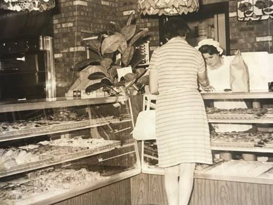A woman purchases pastries in the former Forest Mall