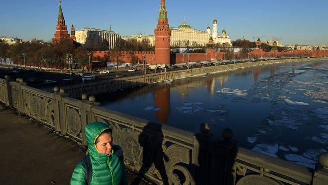 A woman walks along a bridge over the Moskva river near the Kremlin during a sunny winter day in Moscow on Feb. 2, 2017.