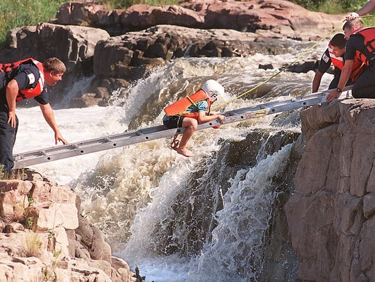 An 8-year-old boy makes his way across the falls to