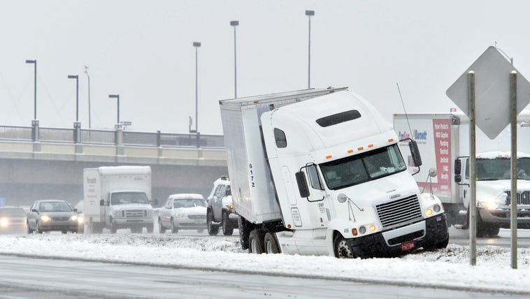 A tractor-trailer sits on the side of a road after