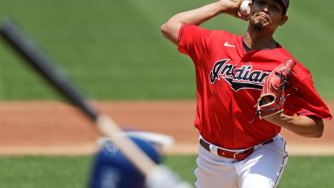 Cleveland Indians starting pitcher Carlos Carrasco, top, delivers to Kansas City Royals' Whit Merrifield in the first inning  Sunday in Cleveland.