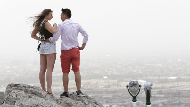 Tim Koo steadies Sonya Grohowski as they look out over El Paso from Scenic Drive Monday afternoon. Strong winds and blowing dust limited the couple's sight seeing during their cross-country road trip from Philadelphia to Seatle.