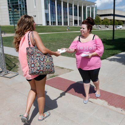 Jessica Lawson, right, hands out fliers on the MSU