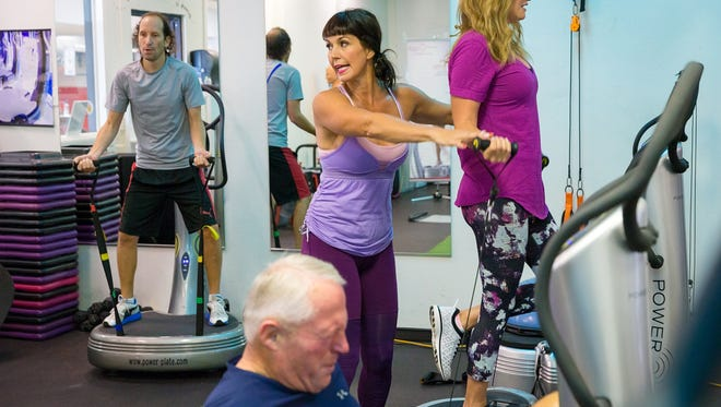 Power plates fitness instructor Christine Androff, center, guides Naples residents Noam Goldberg, from left, Mike Walker and Danielle Otto through a workout at Jabz Health & Fitness in North Naples on Friday, Sept. 9, 2016. The power plate workout machine uses vibrations to engage muscles to intensify a workout.