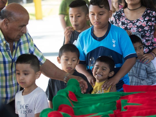 Israel Suarez, CEO of the Nations Association Charities hands out gifts to children at his annual holiday meal at Schandler Park in Fort Myers on Monday.