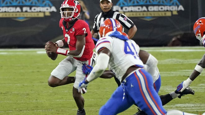 Georgia quarterback D'Wan Mathis (2) looks for a receiver as he is pressured by Florida linebacker James Houston IV (41) during the second half of Saturday's Florida-Georgia game.