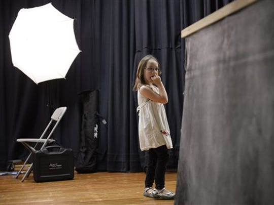 First-grader Riva Roy-Ehri pauses on stage after having her picture made during picture day at Templeton Elementary School in Bloomington, Ind., Tuesday, Sept. 15, 2015.