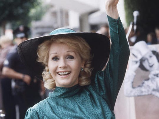 "FILE- In this Feb. 15, 1984, file photo, actress Debbie Reynolds appears at Hollywood Walk of Fame ceremonies in Los Angeles. Reynolds, star of the 1952 classic ""Singin' in the Rain"" died Wednesday, Dec. 28, 2016, according to her son Todd Fisher. She was 84."