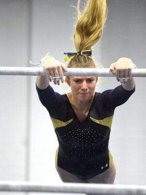 Woodstock Academy's Lydia Taft competes on the bars during the ECC Gymnastics championships at Deary Gymnastics in Danielson.