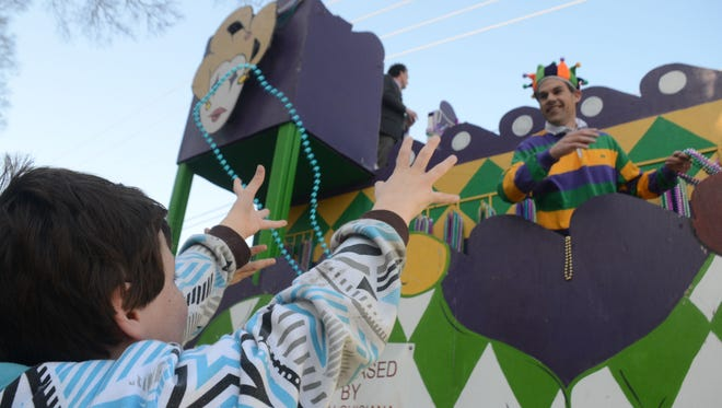 Aiden Burke catches beads from a passing float Saturday at the Alexandria Children's Mardi Gras Parade in downtown Alexandria.
