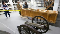 A cannon on a carriage and a crated cannon barrel are