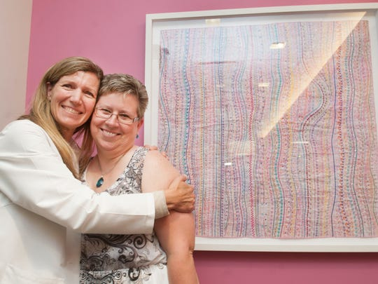 Carolyn Shelby, a breast cancer survivor from Westampton (right), receives a hug from Dr. Kristin Brill, a breast surgeon and program director of the Janet Knowles Breast Cancer Center and division director of breast surgery at Cooper University Hospital in Camden. Behind them is Shelby's 'Journey of Hope,' a fiber art work.