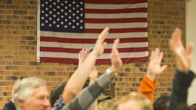 Voters raise their hands to be counted during the Democratic caucus at Rocky Mountain High School in Fort Collins Tuesday. Voters decided Tuesday the state will have a presidential primary going forward.