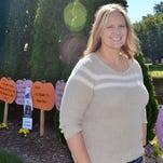 Jessica Honish stands next to display of myths about domestic violence she organized at the Claude Allouez marker along Brazeau Avenue, to increase awareness of the problem during Domestic Violence Awareness Month. She is being honored with a state award this week for her work on behalf of its victims.