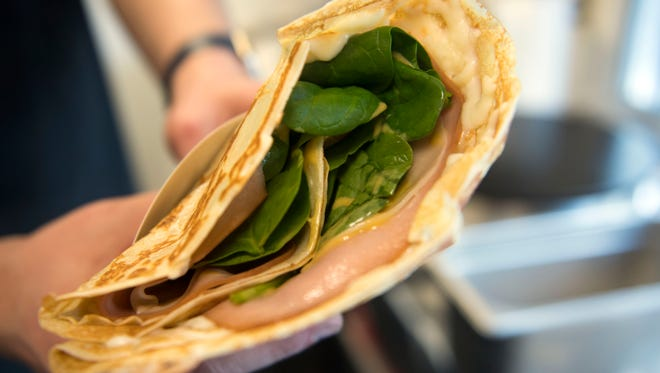 Alex Koshelev holds a smoked turkey crepe, one of the more popular dishes he sells from his food truck, Smart Crepes.