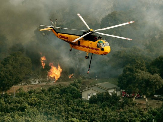 Firefighting helicopters try to save a house from the Thomas wildfire in Carpinteria, Calif. on Dec. 10, 2017. The Thomas fire is only 15 percent contained, now threatening the city of Santa Barbara and the nearby coastal town of Carpinteria, making it one of the worst wildfires in California history.