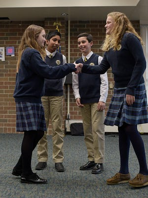 Debaters Tess McNulty (left) and Ella Thompson shake hands after the debate at Detroit Country Day Middle School.   In the background are Abhiniav  Reddy (left) and Nicholas Kalkanis.