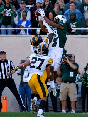 Michigan State's Felton Davis III catches a TD pass over Iowa's Michael Ojemudia, left, and Amani Hooker (27) in the first half Saturday, Sept. 30, 2017 in East Lansing.