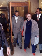 Mike Tyson holds his foster mother's hand as he walks through a metal detector while leaving Marion Superior Court, during his trial for rape in Indianapolis on Feb. 7, 1992. Tyson had to use this exit, because of the throng of media gathered outside the courtroom.