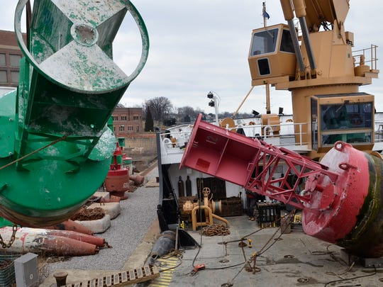 Crew members guide a summer buoy as they unload the ship and place the buoy in storage Saturday, Dec. 20 in Marysville.