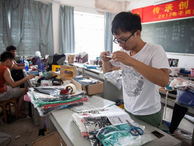Meng Longfei photographs receipts and goods for archive at the Institute of Entrepreneurship at Yiwu Industrial and Commercial College in Yiwu City.