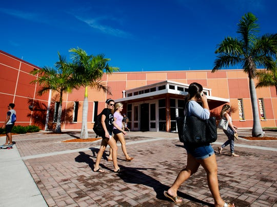 Florida Gulf Coast University students walk between buildings in the South Village housing complex on Wednesday.