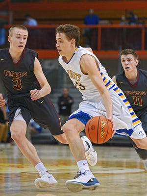 O'Gorman's Matt Cartwright (23) dribbles past Harrisburg's Chase Altenburg (3) during a 2017 SDHSAA Class AA State Boys Basketball quarterfinal game Thursday, March 16, 2017, at Rushmore Plaza Civic Center in Rapid City. O'Gorman beat Harrisburg 61-47.