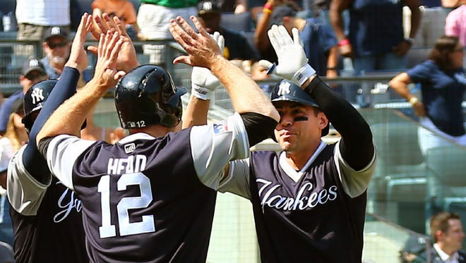 Jacoby Ellsbury and Chase Headley celebrate after Ellsbury's three-run home run in the fourth inning against the Mariners Saturday at Yankee Stadium.