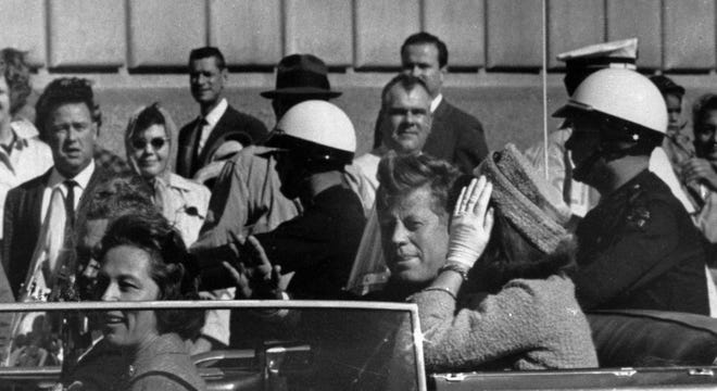 President John F. Kennedy rides in a motorcade with first lady Jacqueline Kennedy before he was shot in Dallas.