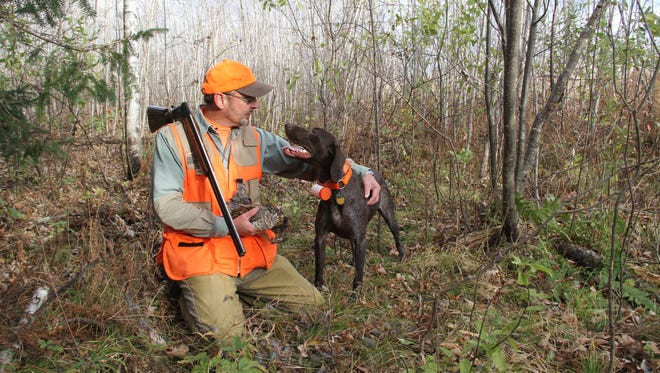 Dan Dessecker of Rice Lake holds a ruffed grouse brought to him by Blu, his German short-haired retriever, on a ruffed grouse hunt in 2011 in Rusk County. Dessecker retired in May from the Ruffed Grouse Society after 30 years with the organization.