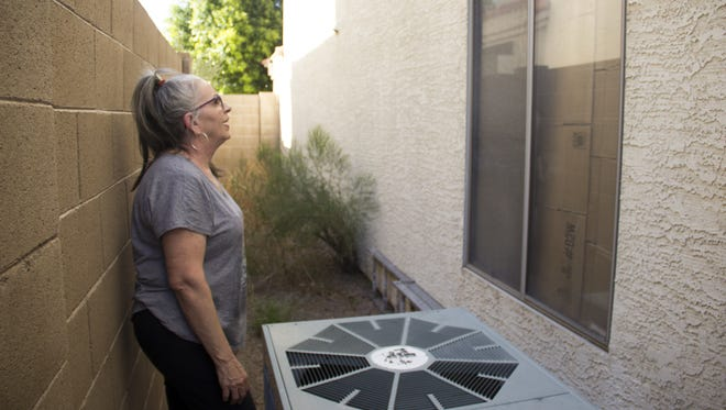 J. Lily Keohane, 64, next to her broken AC unit, examines her house's windows. Keohane spent an afternoon cutting up cardboard boxes to cover almost all of the windows in her house to help protect her from the heat.
