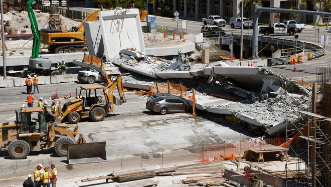 Crushed cars are shown under a section of a collapsed pedestrian bridge, Friday, March 16, 2018 near Florida International University in the Miami area. The new pedestrian bridge that was under construction collapsed onto a busy Miami highway Thursday afternoon, crushing vehicles beneath massive slabs of concrete and steel, killing and injuring several people, authorities said.